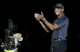 Golfer Tiger Woods applauds as he stands near the golf bag of fellow golfer Rory McIlroy during a golfing demonstration Monday, Aug. 18, 2014, in Jersey City, N.J. (AP Photo/Mel Evans)