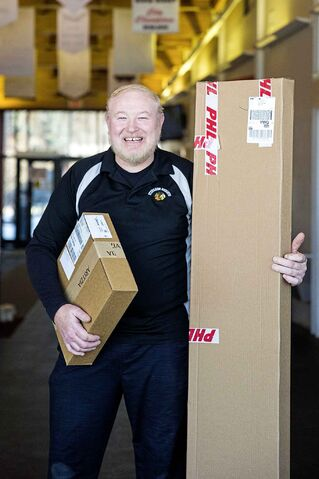 MIKAELA MACKENZIE / WINNIPEG FREE PRESS    Barry Chambers, facility manager at Sturgeon Heights Community Centre, poses for a portrait with packages in Winnipeg on Wednesday, Dec. 11, 2019. The enterprising community centre began accepting packages for pickup last month. For Maggie Macintosh story.  Winnipeg Free Press 2019.