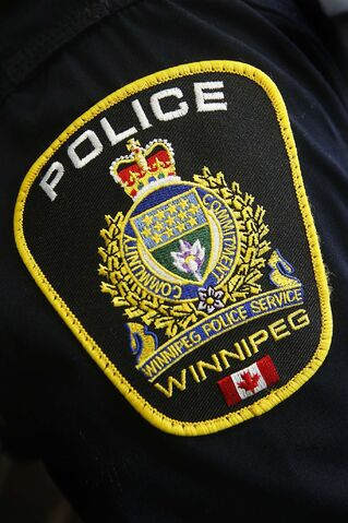 A Winnipeg Police Service shoulder badge on an officer is shown in Winnipeg, Tuesday, November 5, 2019. Police in Winnipeg say a months-long investigation stemming from two murders linked to a dispute between gangs has ended with 11 people being arrested.THE CANADIAN PRESS/John Woods</p>