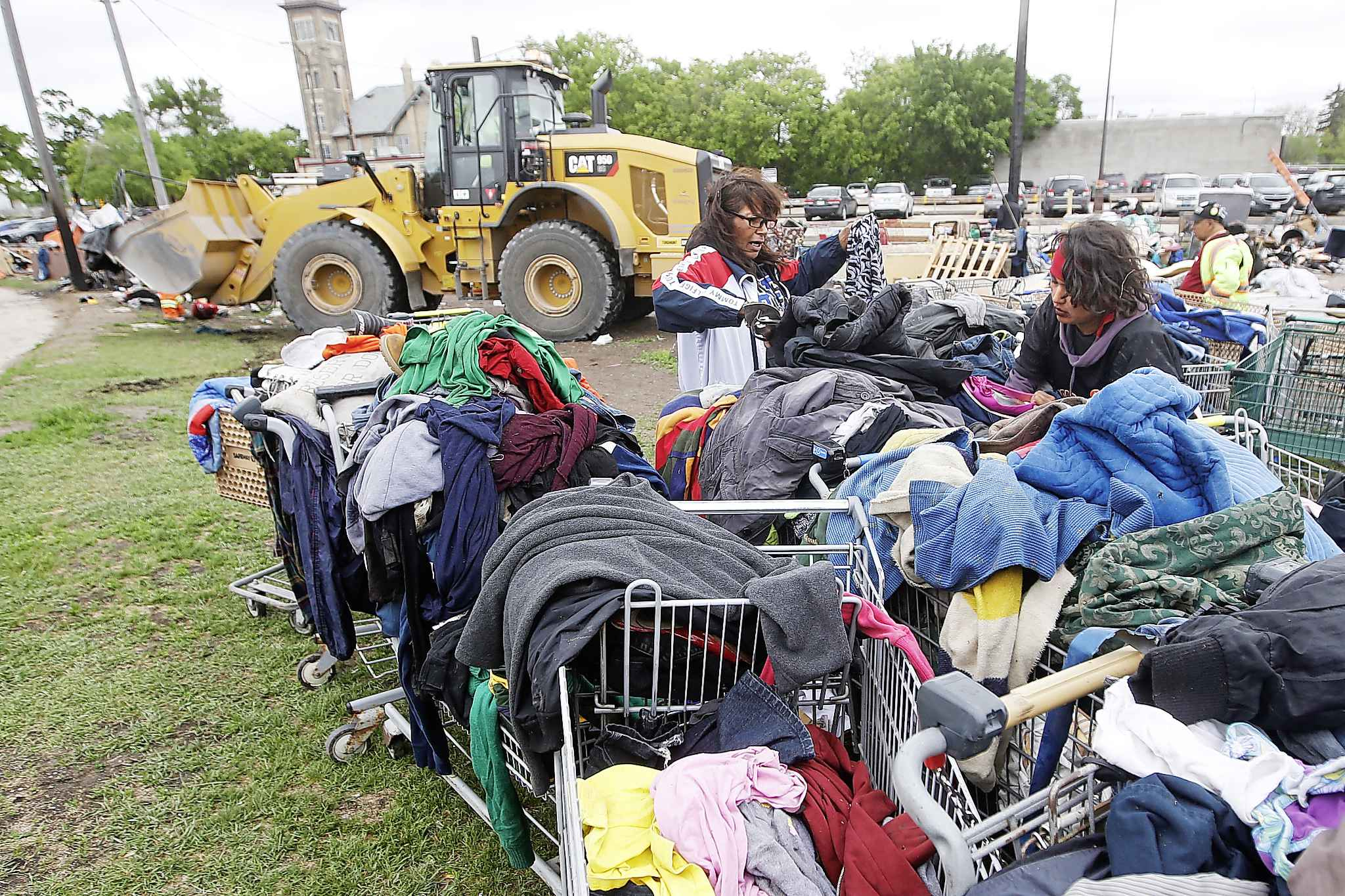 Desirae (right) and another resident look through carts of clothing as city crews dismantle camps.