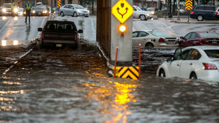 A truck powers through the flooded underpass at Higgins and Main Street, past abandoned cars, around 8pm Thursday night.  