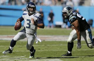 Carolina Panthers defensive tackle Star Lotulelei (98) pursues Seattle Seahawks quarterback Russell Wilson (3) during the second half of an NFL football game, Sunday, Oct. 26, 2014, in Charlotte. (AP Photo/Chuck Burton)