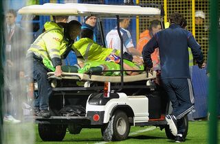 Medics transport Russian goalkeeper Igor Akinfeev after was hit by a flare thrown from the stands during the Euro 2016 Group G qualifying soccer match between Montenegro and Russia, at the City Stadium in Podgorica, Montenegro, Friday, March 27, 2015. (AP Photo/Risto Bozovic)