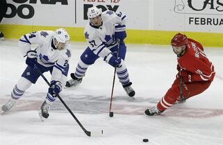 Toronto Maple Leafs' Peter Holland (24) and Brandon Kozun (67) chase the puck with Carolina Hurricanes' Jay McClement (18) during the third period of an NHL hockey game in Raleigh, N.C., Friday, Feb. 20, 2015. McClement has agreed to a two-year contract extension with the Hurricanes. THE CANADIAN PRESS/ AP/Gerry Broome