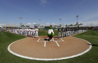 The Philadelphia Phillies mascot Phanatic stands at home plate during the national anthem before a spring training baseball exhibition game against the New York Yankees, Tuesday, March 3, 2015, in Clearwater, Fla. (AP Photo/Lynne Sladky)