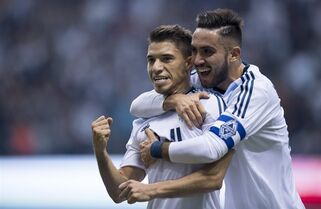 Vancouver Whitecaps FC's Nicolas Mezquida, left, celebrates his goal with teammate Pedro Morales against the Portland Timbers during the first half of MLS soccer action in Vancouver, B.C. Saturday, March 28, 2015. THE CANADIAN PRESS/Jonathan Hayward