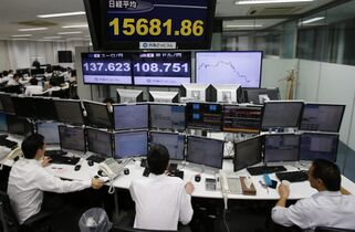 Employees at a foreign exchange brokerage sit at a computer terminal under electric boards flashing the current figures of Japanese yen against dollar and stock market in Tokyo, Thursday, Oct. 2, 2014. Asian stocks fell Thursday amid worries about the strength of U.S. and European recoveries and the first American case of Ebola. Japan's Nikkei 225 index lost 1.7 percent to 15,815.45 points. (AP Photo/Shuji Kajiyama)