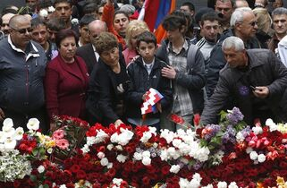 People lay flowers at a memorial to Armenians killed by the Ottoman Turks, as they mark the centenary of the mass killings, in Yerevan, Armenia, Friday, April 24, 2015. On Friday, Armenians mark the centenary of what historians estimate to be the slaughter of up to 1.5 million Armenians by Ottoman Turks, an event widely viewed by scholars as genocide. Turkey, however, denies the deaths constituted genocide and says the death toll has been inflated. (AP Photo/Sergei Grits)