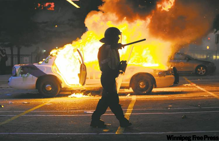 A Vancouver police officer is silhouetted in front of burning car in the city's hockey riot.