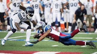 Montreal Alouettes' Brandon Whitaker (2) dives for extra yards as Toronto Argonauts' Dwight Anderson moves in during first half CFL football action in Montreal on August 1, 2014. Tom Higgins concedes it's an important contest but isn't calling the Montreal Alouettes' game with the Toronto Argonauts on Saturday a must-win. The Argos, Alouettes and Hamilton Tiger-Cats all enter weekend action tied atop the East Division standings with identical 6-8 records. THE CANADIAN PRESS/Graham Hughes