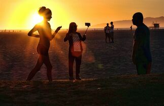 """In this Friday, March 27, 2015 photo, a beachgoer using a cell phone on a stick snaps a selfie as the sun sets at Venice beach in Los Angeles. You can bring your beach towels and floral headbands, but forget that selfie stick if you're going to the Coachella or Lollapalooza music festivals. The sticks are banned this year at the events in Indio, California, and Chicago. Coachella dismissed them as """"narsisstics"""" on a list of prohibited items."""