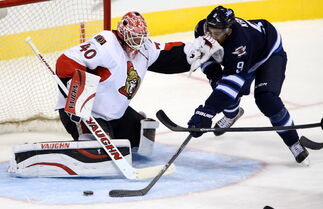 Ottawa Senators goaltender Robin Lehner (40) shoves Winnipeg Jets' Evander Kane (9) as he tries to get a shot away during first period pre-season NHL hockey action in Winnipeg Tuesday.