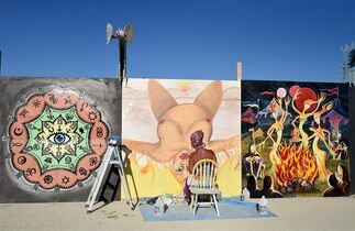 Artist Christina Minor paints on one of the panels around center camp at Burning Man in the Black Rock Desert in Gerlach, Nev. on Aug. 24, 2014, a day before the event opens to ticket holders. (AP Photo/Reno Gazette-Journal, Andy Barron) NO SALES; NEVADA APPEAL OUT; SOUTH RENO WEEKLY OUT