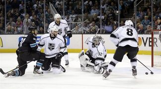 Los Angeles Kings' Drew Doughty (8) clears out a shot on goal next to goalie Jonathan Quick, center, and San Jose Sharks' T.J. Galiardi, left,during the first period in Game 4 of the Western Conference semifinals in the NHL hockey Stanley Cup playoffs in San Jose, Calif., Tuesday, May 21, 2013. (AP Photo/Marcio Jose Sanchez)