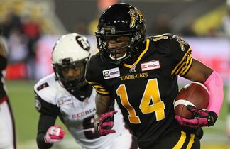 Hamilton Tiger-Cats' Terrell Sinkfield carries the ball while covered by Ottawa Redblacks' Eddie Elder, during second half CFL action in Hamilton, Ontario on Friday, Oct. 17, 2014. THE CANADIAN PRESS/Dave Chidley