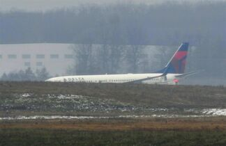 A Delta plane sits on the runway with back door open, where passengers exited after the plane slid off the runway at Detroit Metropolitan Airport on Saturday, Nov. 22, 2014 in Romulus, Mich. Airport spokesman Michael Conway said all four parallel runways have reopened but flights stopped for a couple hours Saturday morning when the entire airfield