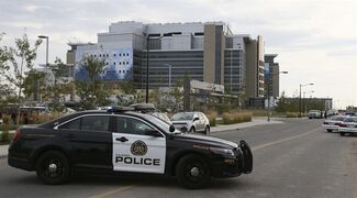 Calgary Police block the entrance to the South Calgary Health Campus as they search for cougars on Thursday, Sept 18, 2014 in Calgary. THE CANADIAN PRESS/Mike Ridewood