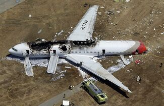 File - In this July 6, 2013, aerial file photo, the wreckage of Asiana Flight 214 lies on the ground after it crashed at the San Francisco International Airport in San Francisco. On Tuesday, March 3, 2015, more than 70 passengers aboard an Asiana Airlines flight that crashed in San Francisco two years ago have reached a settlement in their lawsuits against the airline. (AP Photo/Marcio Jose Sanchez, File)