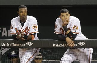 Baltimore Orioles' Adam Jones, left, and Manny Machado watch from the dugout in the 10th inning of a baseball game against the Los Angeles Angels, Thursday, July 31, 2014, in Baltimore. Los Angeles won 1-0 in 13 innings. (AP Photo/Patrick Semansky)
