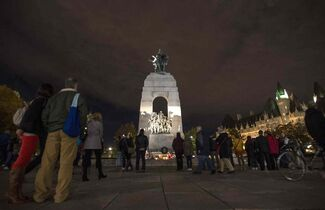People take in the memorial at the Tomb of the Unknown Soldier near Parliament Hill in Ottawa on Thursday, where Cpl. Nathan Cirillo, 24, was killed by a gunman.