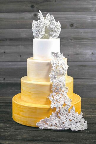 The edible wedding cake topper was made with a 3D printer to look like the veil of the bridal gown.