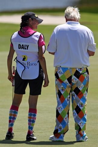 Caddy Anna Cladakis smiles while watching John Daly write in his scorecard, after finishing the first round of the Puerto Rico Open PGA golf tournament in Rio Grande, Puerto Rico, Thursday, March 5, 2015. (AP Photo/Ricardo Arduengo)