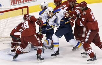 St. Louis Blues' David Backes (42) scores a goal against Arizona Coyotes' Mike Smith (41) as they are surrounded by Coyotes' Lauri Korpikoski (28), of Finland, Martin Hanzal (11), of the Czech Republic, Michael Stone (26) and Chris Summers as Blues' Vladimir Tarasenko (91), of Russia, creates a screen in front of the net during the first period of an NHL hockey game Saturday, Oct. 18, 2014, in Glendale, Ariz. (AP Photo/Ross D. Franklin)