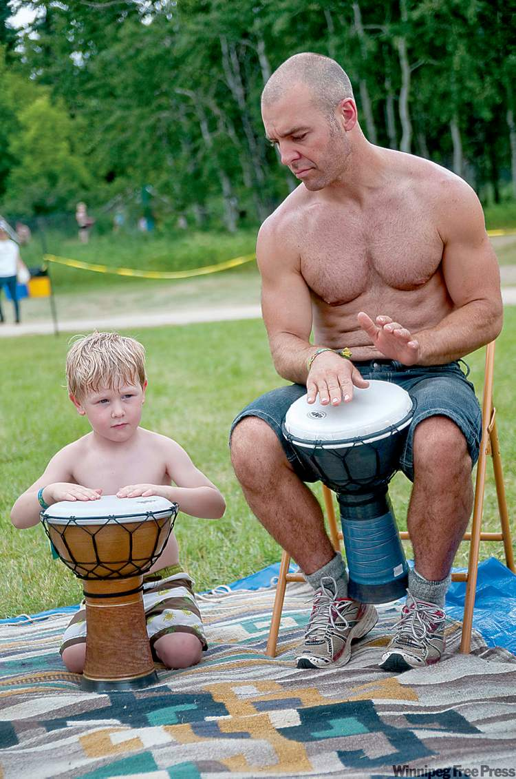 Monty Wensel and his 5-year-old son, Imari, partake in a drumming circle at the Folk Fest on Saturday. July 9, 2011. (HADAS PARUSH / WINNIPEG FREE PRESS)