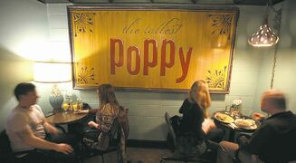 A sign that was formerly on the outside of the Tallest Poppy�s Main Street location now hangs inside its new location.