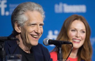 Director David Cronenberg, left, and actor Julianne Moore laugh during a press conference for