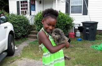 In this Monday, July 21, 2014 photo, Regina Harrell, 9, holds her dog Roscoe outside her home, in North Augusta, S.C. Regina was taken from her home and her mother charged with a felony after her mother, Debra Harrell, left her alone to play at a nearby park while she worked at McDonald's. (AP Photo/Jeffrey Collins)