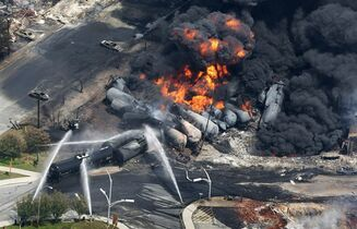 FILE - In this July 6, 2013 file photo, smoke rises from railway cars carrying crude oil after derailing in downtown Lac Megantic, Quebec. American Petroleum Institute President Jack Gerard said Tuesday that the oil and railroad industries are urging federal regulators to allow them as long as seven years to retrofit existing tank cars that transport highly volatile crude oil. (AP Photo/The Canadian Press, Paul Chiasson, File)