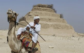 Hussien Ahmed, 70, a camel rider, talks to a visitor in front of the Djoser Pyramid, 30 kilometers southwest of Cairo, in Saqqara, Egypt, Sept. 16, 2014. The restoration of the 4,600-year old pyramid has prompted controversy between the Ministry of Antiquities, activists and archaeologists. (AP Photo/Amr Nabil)