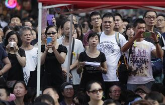 Local residents join a a pro-democracy sit in at a main intersection in the Mongkok district in Hong Kong, Wednesday, Oct. 1, 2014. Student leaders of pro-democracy protests in Hong Kong warned Wednesday that if the territory's leader doesn't resign by the end of Thursday they will step up their actions, including occupying several important government buildings. (AP Photo/Wally Santana)