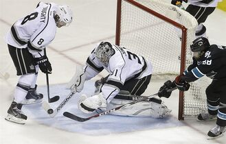 Los Angeles Kings goalie Martin Jones, center, blocks a shot during the third period of Game 1 of an NHL hockey first-round playoff series against the San Jose Sharks Thursday, April 17, 2014, in San Jose, Calif. At left is Kings' Drew Doughty (8), at right Sharks' Brent Burns. (AP Photo/Ben Margot)