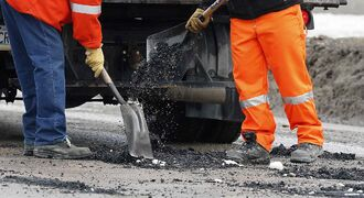 A city crew repairs potholes on St. James Street.