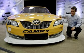 Daniel Suarez poses by his car during a news conference at Joe Gibbs Racing's headquarters in Huntersville, N.C., Tuesday, Aug. 19, 2014. Joe Gibbs Racing has hired Carl Edwards to drive a new fourth Sprint Cup car in 2015 and Daniel Suarez will drive in the Nationwide series. (AP Photo/Chuck Burton)