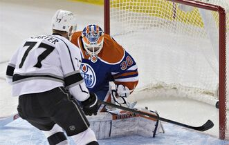 Los Angeles Kings' Jeff Carter (77) scores a goal on Edmonton Oilers goalie Ben Scrivens (30) during second period NHL hockey action in Edmonton, Alta., on Tuesday March 3, 2015. THE CANADIAN PRESS/Jason Franson