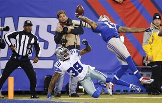 FILE - In this Nov. 23, 2014, file photo New York Giants wide receiver Odell Beckham Jr. (13) makes a one-handed catch for a touchdown against Dallas Cowboys cornerback Brandon Carr (39) in the second quarter of an NFL football game in East Rutherford, N.J. Beckham grabbed The Associated Press NFL Offensive Rookie Of The Year award for 2014. (AP Photo/Kathy Willens, File)