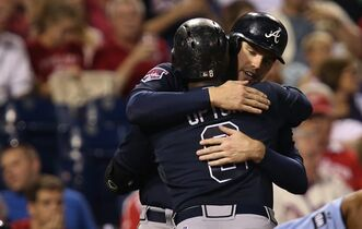 Atlanta Braves Justin Upton, foreground, is embraced by Freddie Freeman after Upton hit a home run in the seventh inning of a baseball game against the Philadelphia Phillies, Saturday, Sept. 27, 2014, in Philadelphia. Atlanta won 4-2. (AP Photo/Laurence Kesterson)