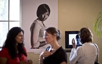 FILE - In this Tuesday, Sept. 16, 2014 file photo, a visitor wearing headphones, right, listens to the video testimony of survivor Irene, who worked at a restaurant in the Westgate Mall and whose portrait hangs on the wall, while other visitors discuss, at the opening of an exhibition of