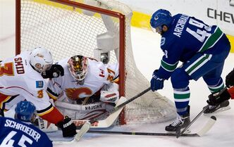 Vancouver Canucks' Darren Archibald, right, digs for the puck and eventually scores against Calgary Flames' goalie Joni Ortio, of Finland, during second period NHL hockey action in Vancouver, B.C., on Saturday March 8, 2014. The Canucks have signed forwards Archibald and Brandon DeFazio. THE CANADIAN PRESS/Darryl Dyck