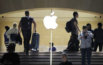 FILE - In this May 11, 2012 file photo, travelers pass the Apple store at New York's Grand Central Terminal. Apple reports quarterly financial results on Monday, April 27, 2015. (AP Photo/Mark Lennihan, File)