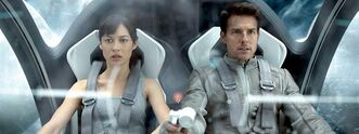 This film publicity image released by Universal Pictures shows Olga Kurylenko, left, and Tom Cruise in a scene from
