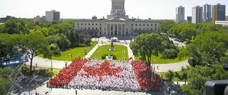 People gather on the Manitoba legislature grounds to make a living flag on Canada Day last year.