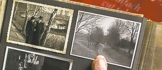 Woelk opens an old photo album, pointing to a picture showing the way to Hitler's command centre in what is now Poland.