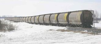 Idle grain cars sit on the tracks south of Kemnay, Man. Slow delivery of last season's bumper grain crop to West Coast ports has $14 billion to $20 billion of it sitting on farms, Ottawa estimates.