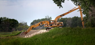 A heavy-equipment operator reinforces a dike on the Assiniboine River between St. Eustache and Portage la Prairie.