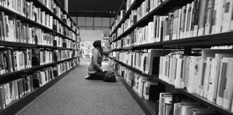 A young woman has a quiet moment in the stacks at the Millennium Library.