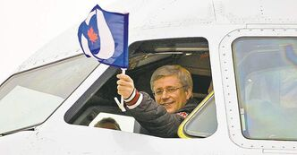 Prime Minister Stephen Harper raises the party banner during campaigning.